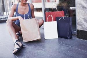 vacker ung flicka sitter med shoppingkassar på gatan och är nöjd med sina nya kläder foto