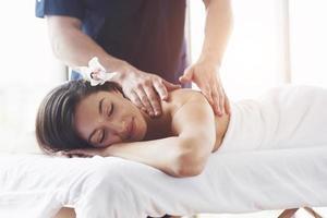 vacker ung kvinna som kopplar av med handmassage på beauty spa. foto
