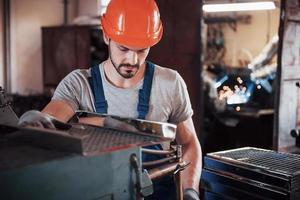 porträtt av en ung arbetare i en hård hatt på en stor metallbearbetningsanläggning. ingenjören servar maskinerna och tillverkar delar till gasutrustning foto