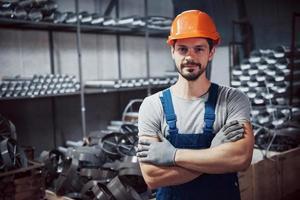 porträtt av en ung arbetare i en hård hatt på en stor metallbearbetningsanläggning. skiftman på lagret av färdiga produkter foto