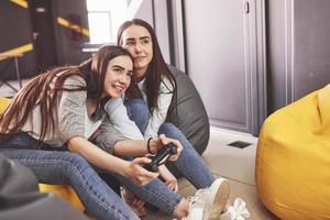 tvillingsyster systrar spelar på konsolen. tjejer håller joysticks i händerna och har kul foto