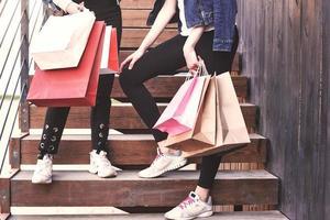 två ung kvinna som bär påsar medan de går i trappan efter att ha besökt butikerna foto
