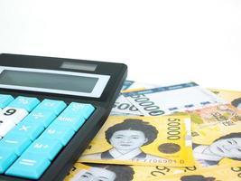 Sydkorea 50000 vann sedelvaluta närbildsmakro med miniräknare isolerad på vit bakgrund, koreanska pengar foto