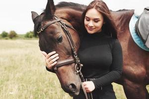 en glad tjej kommunicerar med sin favorithäst. tjejen älskar djur och ridning foto