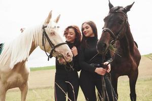 två unga vackra tjejer i redskap för ridning nära sina hästar. de älskar djur foto