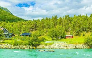 turkos smältvatten rinner i en flod genom byn i norge. foto