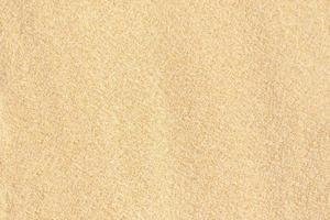 sand textur bakgrund. brunt ökenmönster från tropisk strand. foto