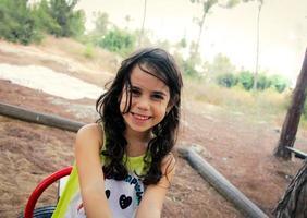 liten flicka leende medan han lekte på lekplatsen i parken foto