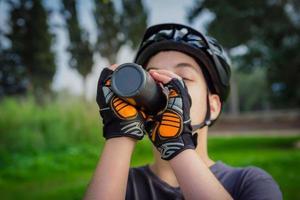 ung pojke med cykelhjälm som dricker från en svart plastflaska foto