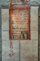 fönster förseglat med röda tegelstenar i en övergiven byggnad foto