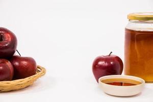 hög med äpplen och rött äpple och burk med honungsskål med honung isolerad på en vit bakgrund foto