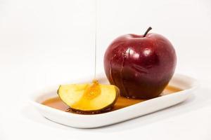 hälla honung på rött äpple och rött äppelskiva på vit tallrik med honung isolerad på en vit bakgrund foto
