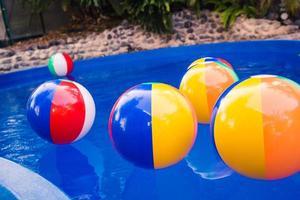 färgglada strandbollar som flyter i poolen foto