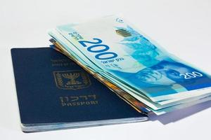 stapel israeliska pengarräkningar på 200 shekel och israeliskt pass foto