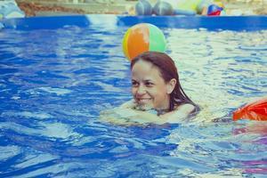 kvinna leker med strandboll i poolen foto