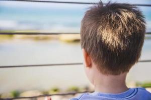 ung pojke ser långt bort till horisonten bakom metallstaket foto