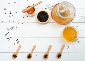 platt lag med varmt te i tekanna och kopp med honung på whotbordet foto