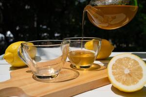 varmt te i tekanna hälldes i tekoppar och serverades på bordet i caféet foto