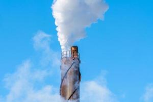 rökstack mot en blå himmel som pumpar ut föroreningar i luften foto