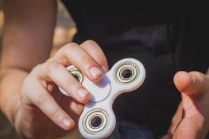 ung flicka leker med fidget spinner foto