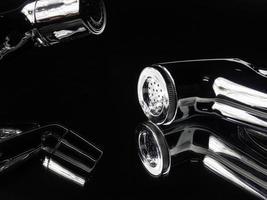 närbild bidé duschmaterial och spiralrör. designkonceptet bygger på en spegelbakgrund med en svart ton som är mycket blank och dyr. rumpa rengöringsutrustning i badrummet foto