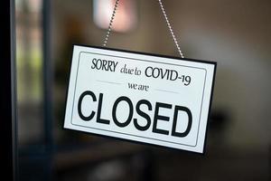 stängd skylt som hänger på dörren till caféet på grund av covid-19 foto