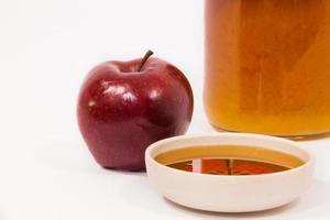 rött äpple och burk med honungsskål honung isolerad på en vit bakgrund foto