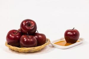 hög med röda äpplen och rött äpple på vit tallrik med honung isolerad på en vit bakgrund foto