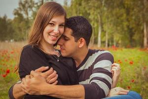 ungt par som sitter på gräset i ett fält av röda vallmo och ler mot kameran foto