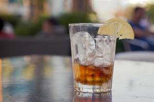glas med cola, is och citron på ett bord utanför foto