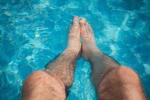 ung man avkoppling vid poolen med benen i vattnet foto