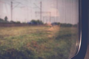 mystiskt kvinnans ansikte med svarta solglasögon reflekterade i fönstret på ett tågtåg foto