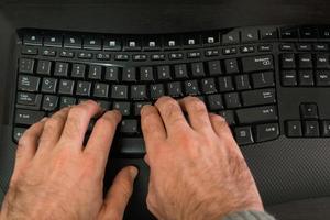 man som skriver på ett tangentbord med bokstäver på hebreiska och engelska foto