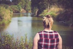 bakifrån av kvinnan som står och tittar bort vid flodens stränder foto