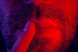 makro närbild på mannen med tankeväckande ansiktsuttryck med fingret mot läpparna foto