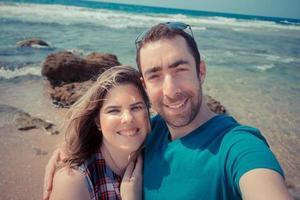 ungt par som tar selfie med smartphone eller kamera på stranden foto
