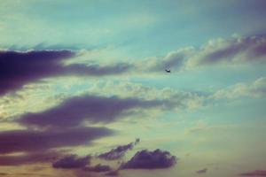 silhuett av ett flygplan som flyger i solnedgångshimlen foto