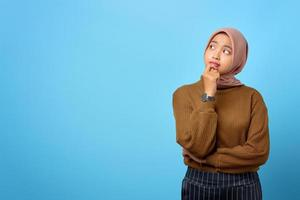 fundersam ung asiatisk kvinna ser seriöst och tänker på en fråga på blå bakgrund foto