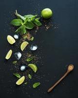 ingredienser för mojito. färsk mynta, limefrukter, is, socker över svart foto