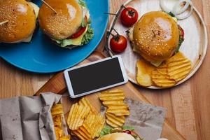 hamburgare med moblie-telefon foto