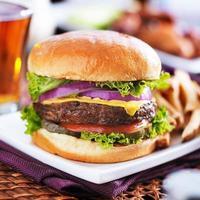 cheeseburger med öl och pommes frites på nära håll