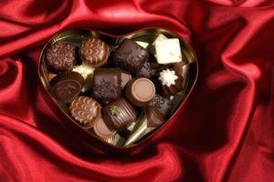 hjärtformad låda med godis på röd satin bakgrund foto