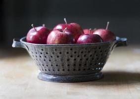 röda läckra äpplen i en antik emaljerad tennfäril foto