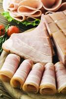 färska skinkskivor med grönsallat och körsbärstomat foto