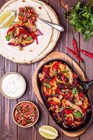 fläsk fajitas med lök och färgad peppar, serveras med tortill foto