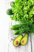 en blandning av gröna grönsaker på ett träbord foto