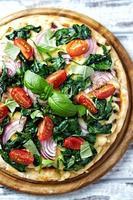 spenatpizza med körsbärstomater foto