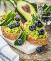 avokadosmörgås och blåbär på träbakgrunden foto