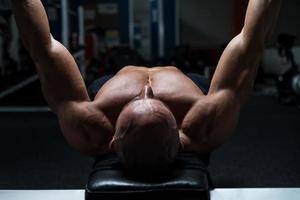 mogen man som tränar i gymmet foto