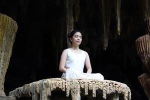 asiatisk kvinna gör meditation i grottan foto
